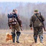 two men walking with dog hunting